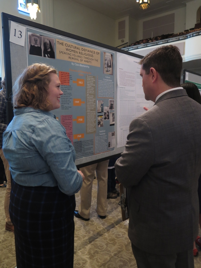 "Ramonat Scholar Claire Blankenship explains her poster, ""The Cultural Defiance of Women Religious,"" to Patrick Green, Director of the Center for Experiential Learning."